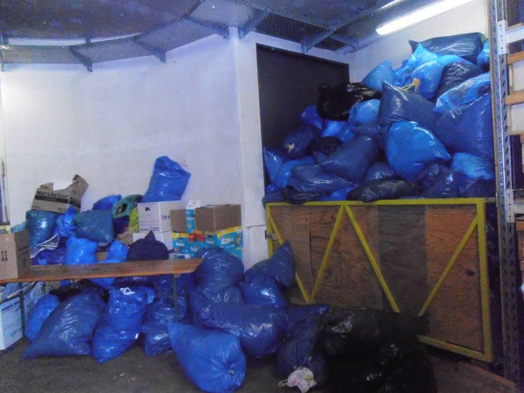 In den blauen Tüten sind Anziehsachen. Wenn Pfarrer Meurer mal wieder in den Medien war gibt es viele Spenden für die Kleiderkammer.