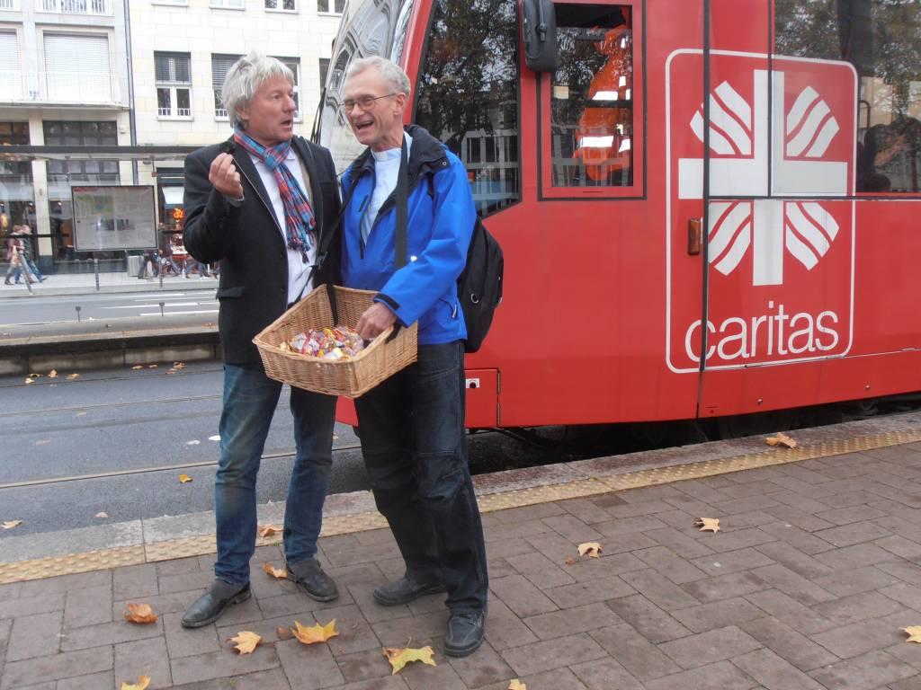 Pfarrer Franz Meurer (rechts) und Kabarettist Jürgen Becker (links) stehen vor der Straßenbahnlinie eins.